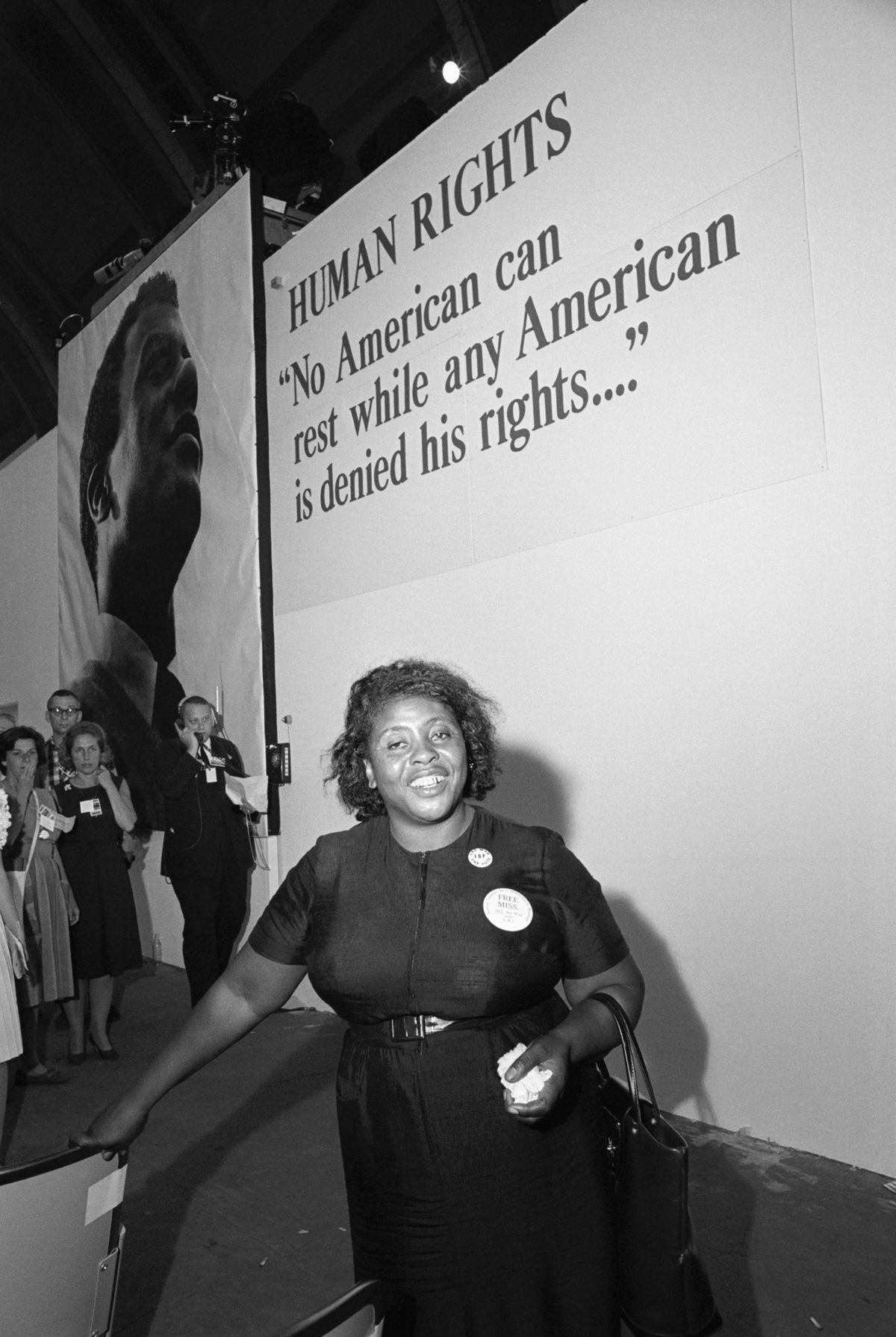 "The activist Fannie Lou Hamer poses for a photo at the 1964 National Democratic Convention in front of a sign reading ""HUMAN RIGHTS No American can rest while any American is denied his rights..."""