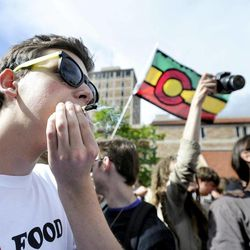 Joe, last name not given, at left, smokes a marijuana cigarette in the crowd during the 4/20 rally on the University of Colorado campus in Boulder, Colo., on Friday, April 20, 2012. Many students at the University of Colorado and other campuses across the country have long observed 4/20. The counterculture observation is shared by marijuana users from San Francisco's Golden Gate Park to New York's Greenwich Village.