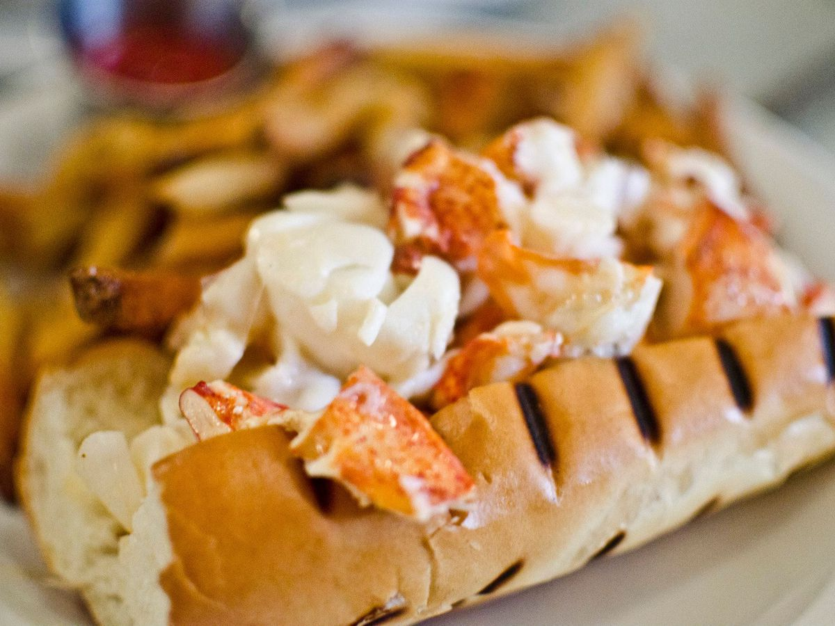 The Maine lobster roll at Neptune Oyster is served on a grilled hot dog bun atop a white plate, and is accompanied by French fries and a ramekin of ketchup.