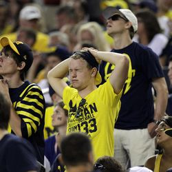 Michigan fans in the stands react to a play during the first half of an NCAA college football game against the Alabama at Cowboys Stadium in Arlington, Texas, Saturday, Sept. 1, 2012.