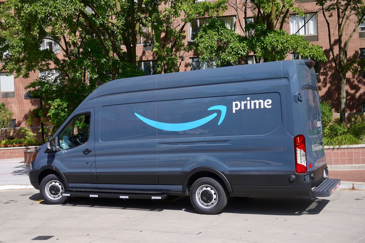 "An Amazon delivery van with the smile logo and the word ""prime"" painted on the side."