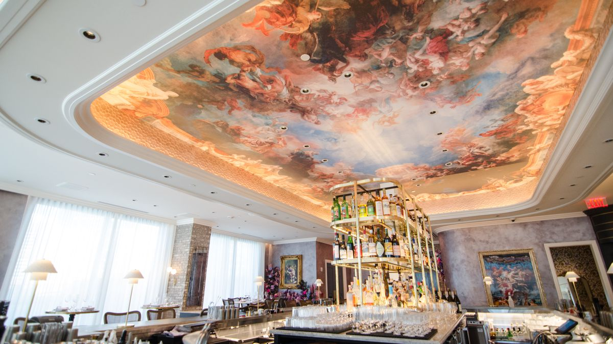 A sun-lit upscale restaurant interior features a massive Renaissance mural painted on the ceiling above the bar.