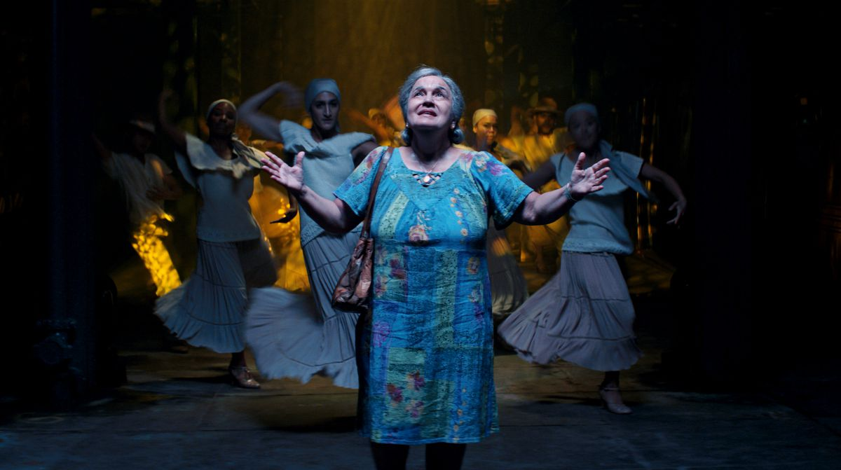 A grandmother stands on a subway platform, lit from the ceiling, with dancers in the background.