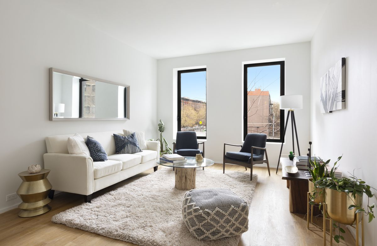 A living area with two large windows, hardwood floors, a white couch, and a round glass coffee table.