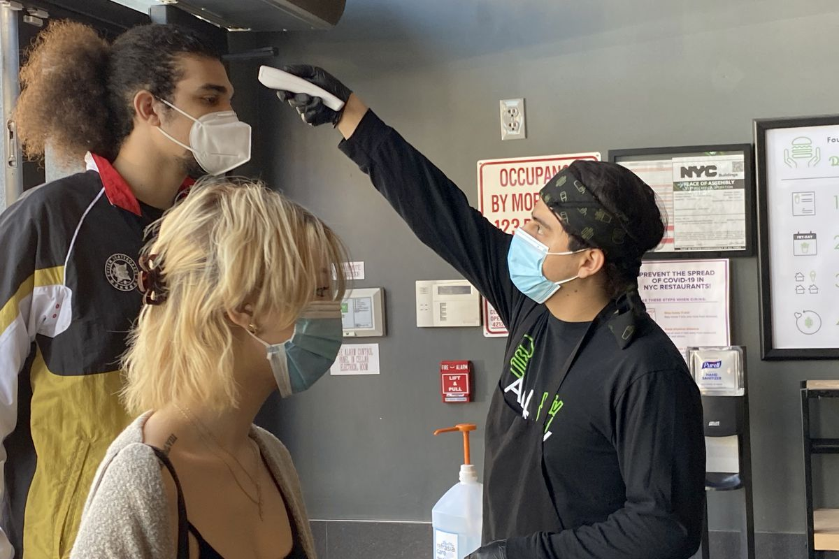 Customer getting temperature taken before entering Shake Shack, as indoor dining begins, Queens, NY
