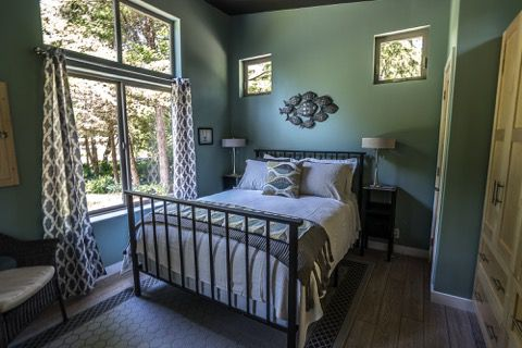 A bedroom with green walls and a bed. There are floor to ceiling windows looking out into a yard. There is art hanging on the wall above the bed.