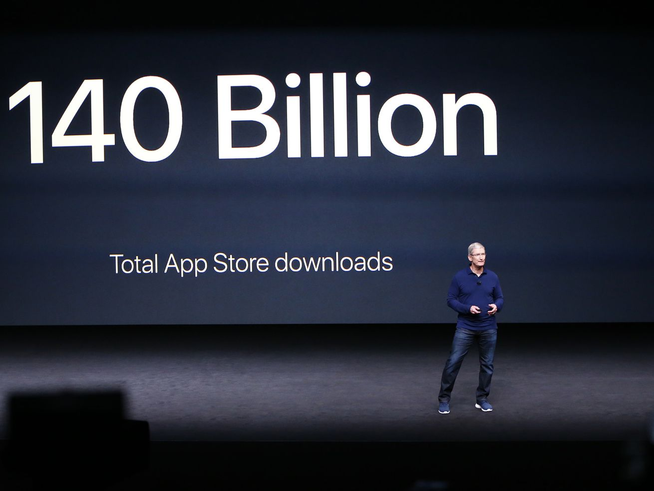 """Apple CEO Tim Cook onstage at an Apple event in front of a large screen that reads """"140 billion total app store downloads."""""""