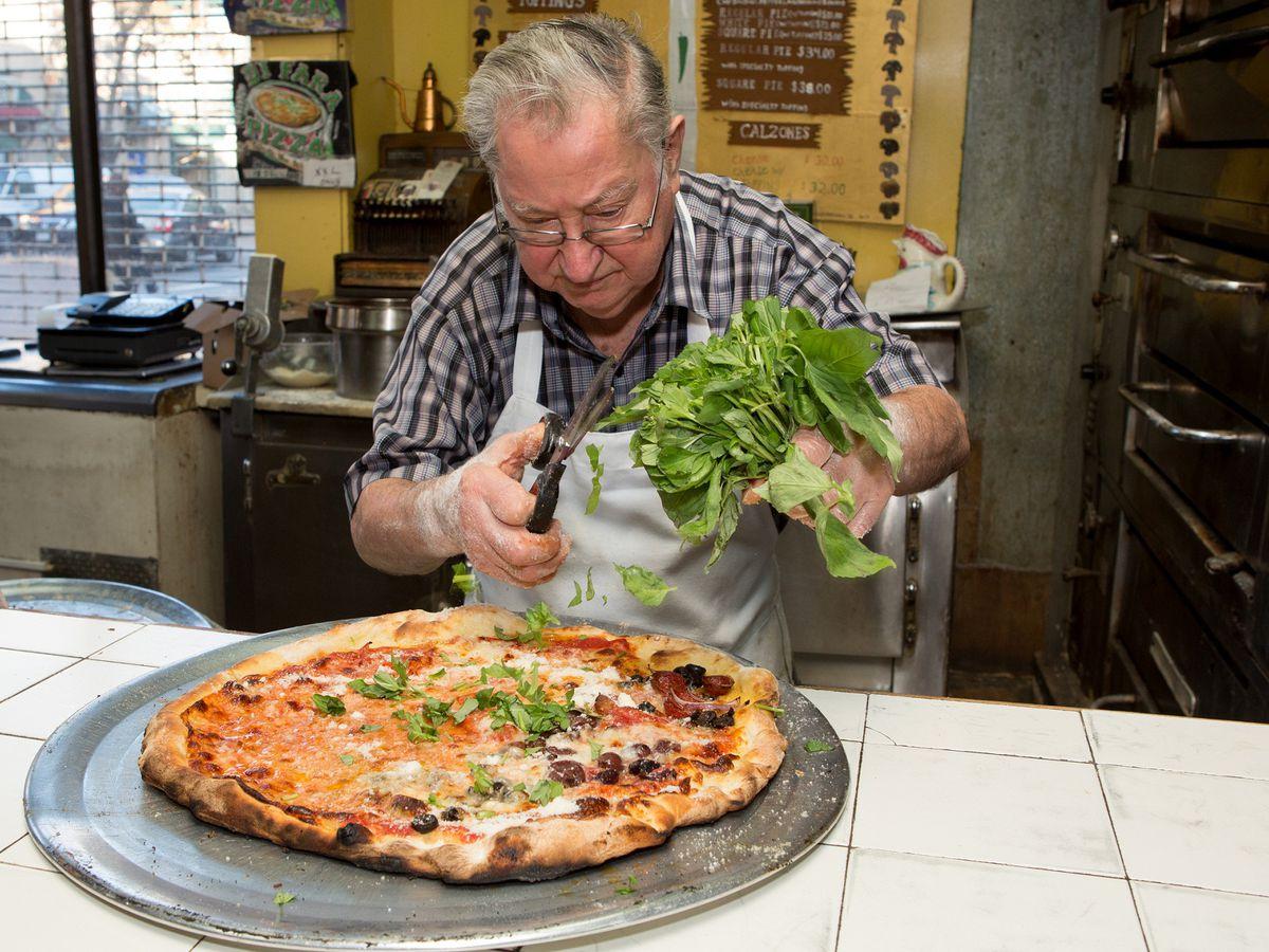 A man makes a pizza