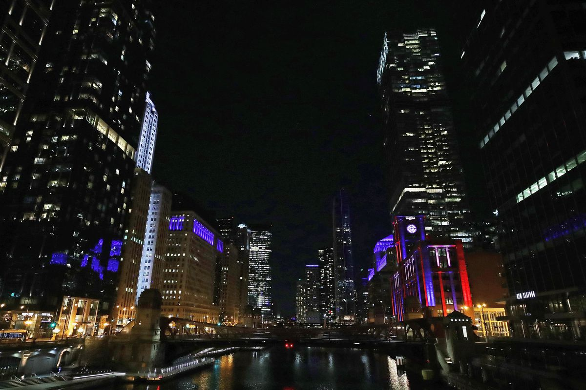 This photo shows the view looking south on the Chicago River as buildings are lit in blue April 9, 2020 to show support for health care workers and first responders.
