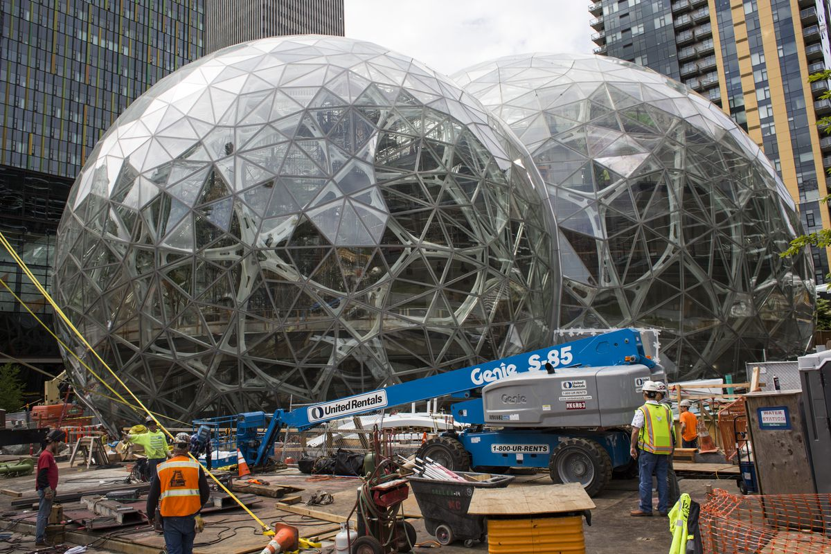Workers surround the signature glass spheres under construction at the Amazon corporate headquarters in Seattle.