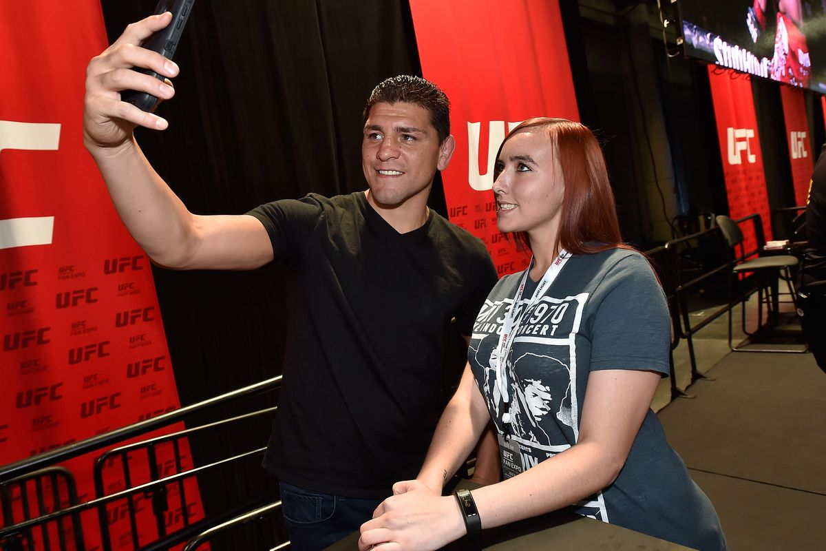 Nick Diaz (L) meets with a fan at the UFC Fan Expo at the Las Vegas Convention Center on July 8, 2016 in Las Vegas, Nevada