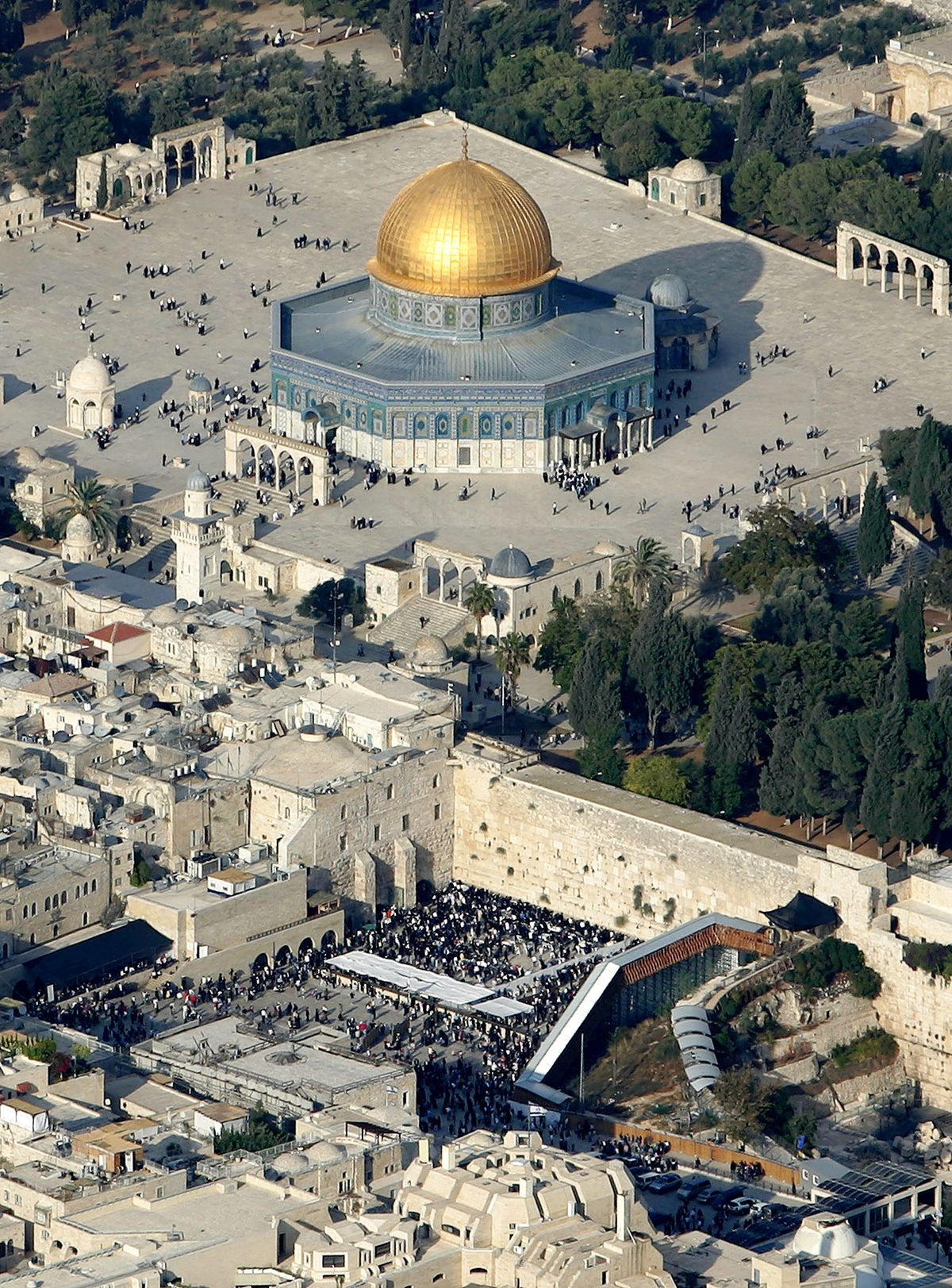 """FILE- In this aerial photo from files dated Oct. 20, 2005, Muslim worshippers gather outside the Dome of the Rock Mosque, in the Al Aqsa Mosque compound, also known to Jews as the Temple Mount, and Jews gather at the Western Wall, bottom center, the holiest site where Jews can pray, in Jerusalem's Old City. Conventional wisdom on Israeli-Palestinian peacemaking has long held that Israel should relinquish most of the lands it occupied in 1967 in favor of a Palestinian state, the """"two-state solution"""" that much of the world has supported for years, but Mohammed Ishtayeh, a senior adviser to Palestinian President Mahmoud Abbas, said on Sunday Dec. 12, 2010 """"If Israel continues with these measures that it is employing today the possibility of a two-state solution becomes very slim"""". (AP Photo/Kevin Frayer, File)"""