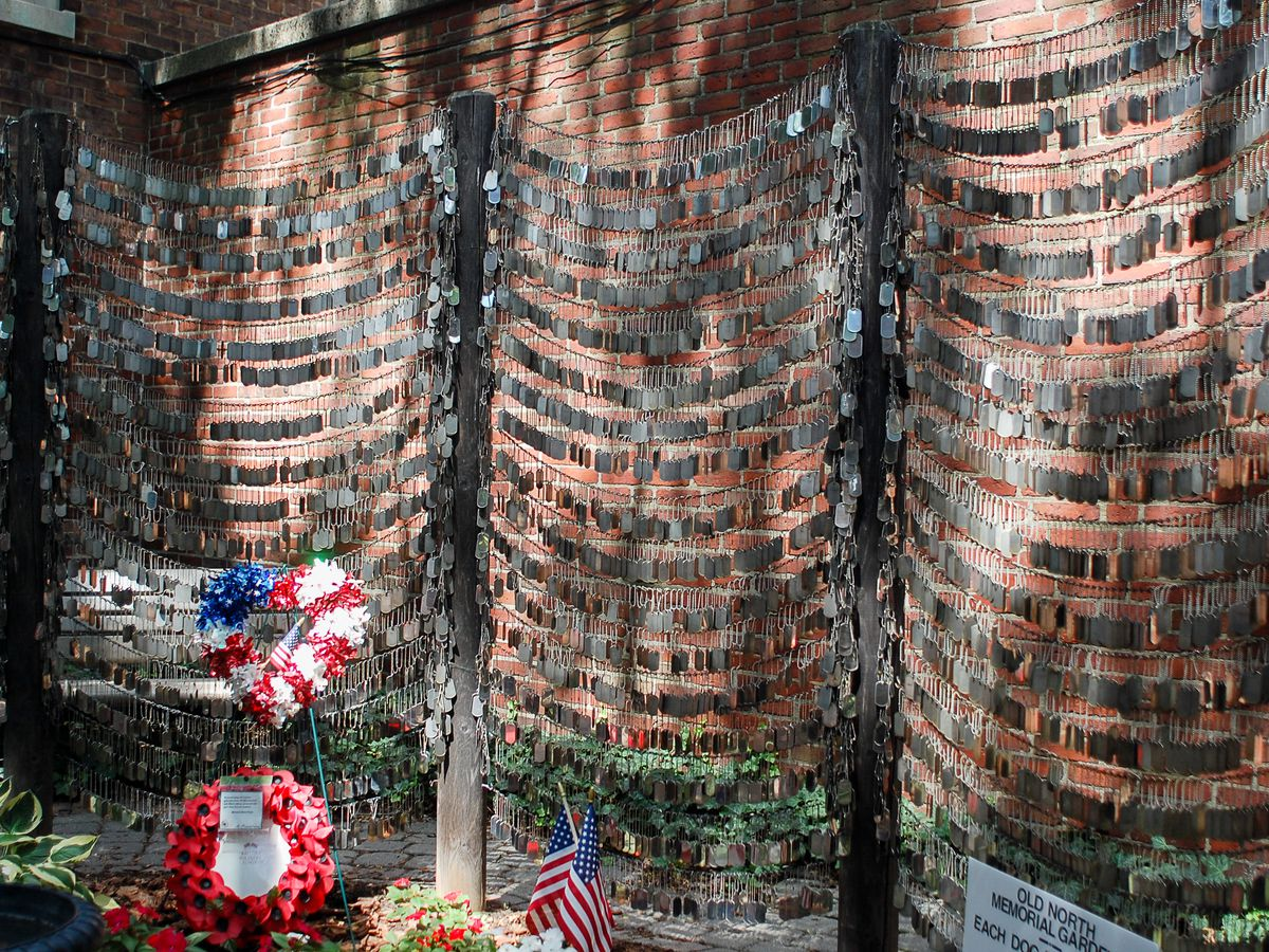 Dozens of dog tags hanging together against a brick background in a memorial garden.