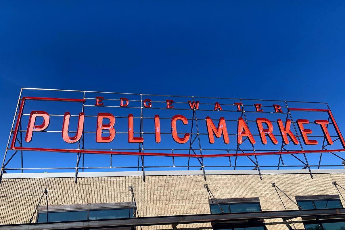 """A photo of a sign reading """"Edgewater Public Market"""" in red letters above the market building"""