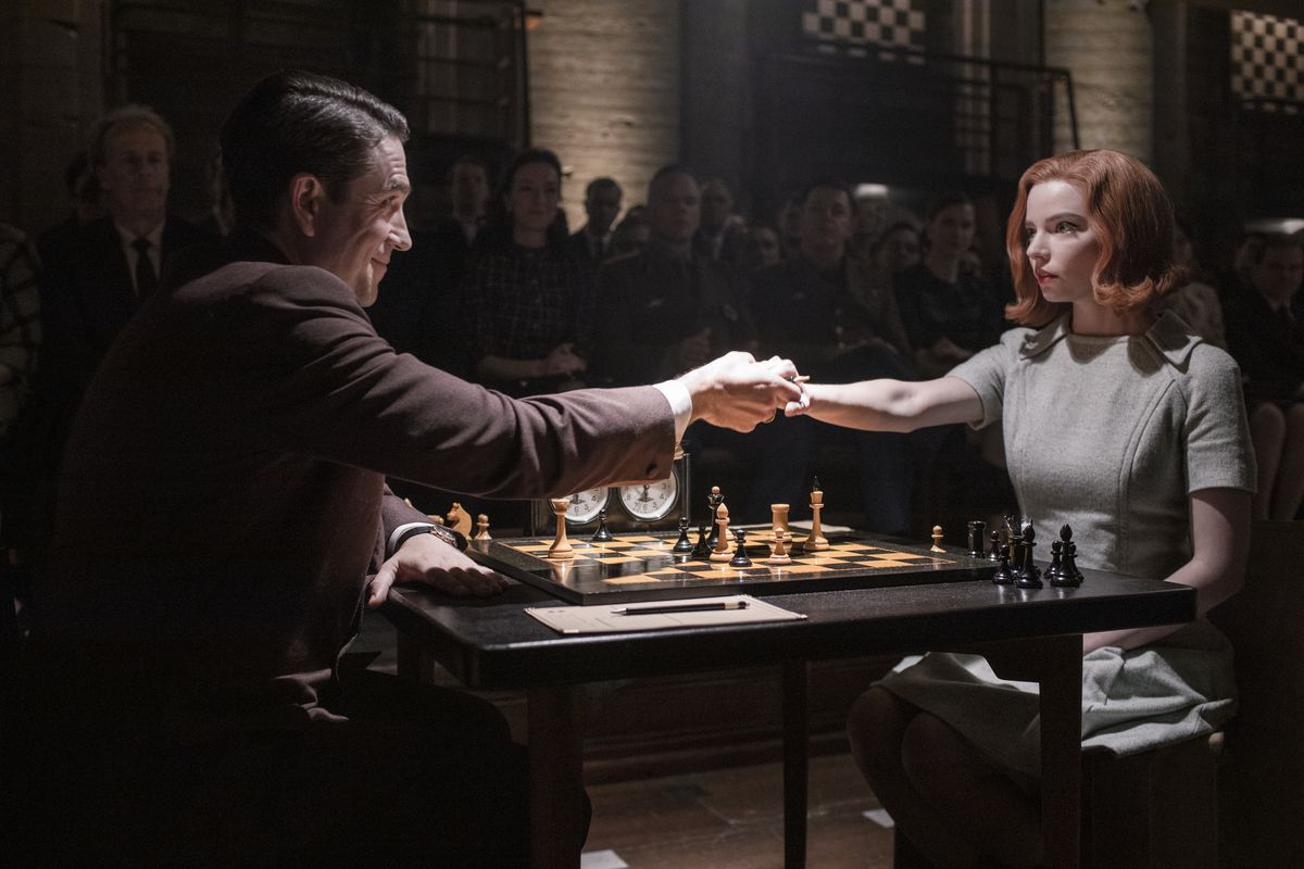 Queen's Gambit: Anya Taylor-Joy shakes a guy's hand over a chess board