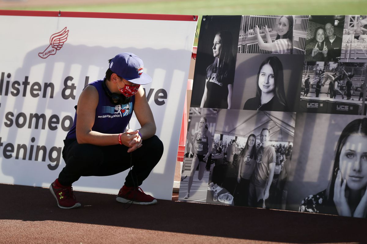 Tastan Sperling, a friend of slain University of Utah student Lauren McCluskey, looks at photos of her during the Lauren McCluskey Memorial Walk at the McCarthey Family Track and Field Complex on the University of Utah campus in Salt Lake City on Thursday, Oct. 22, 2020. McCluskey, a track athlete, was was shot and killed near her dorm by Melvin Shawn Rowland, 37, on Oct. 22, 2018,