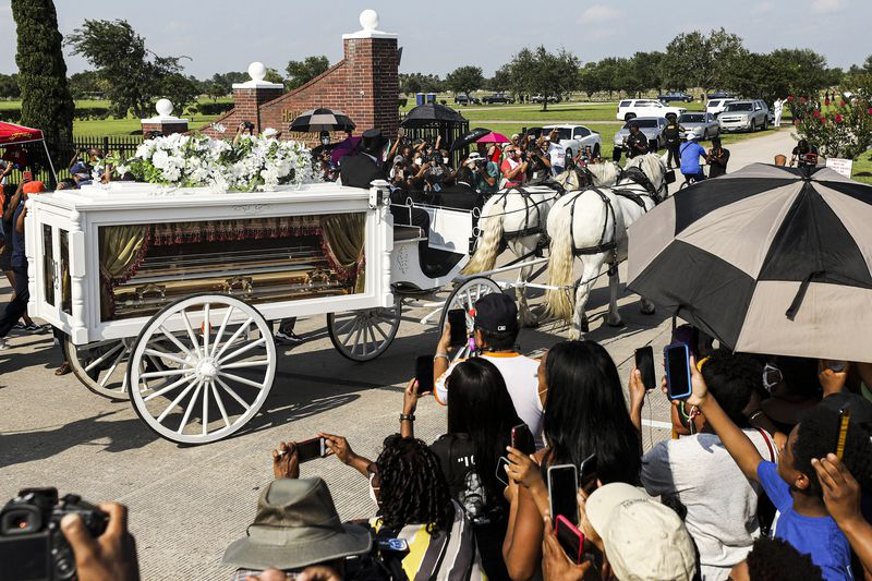 White bourses pull a white carriage with glass sides. Through the glass, a gold coffin is visible. A crowd stands around the carriage, holding up their phones for photos.