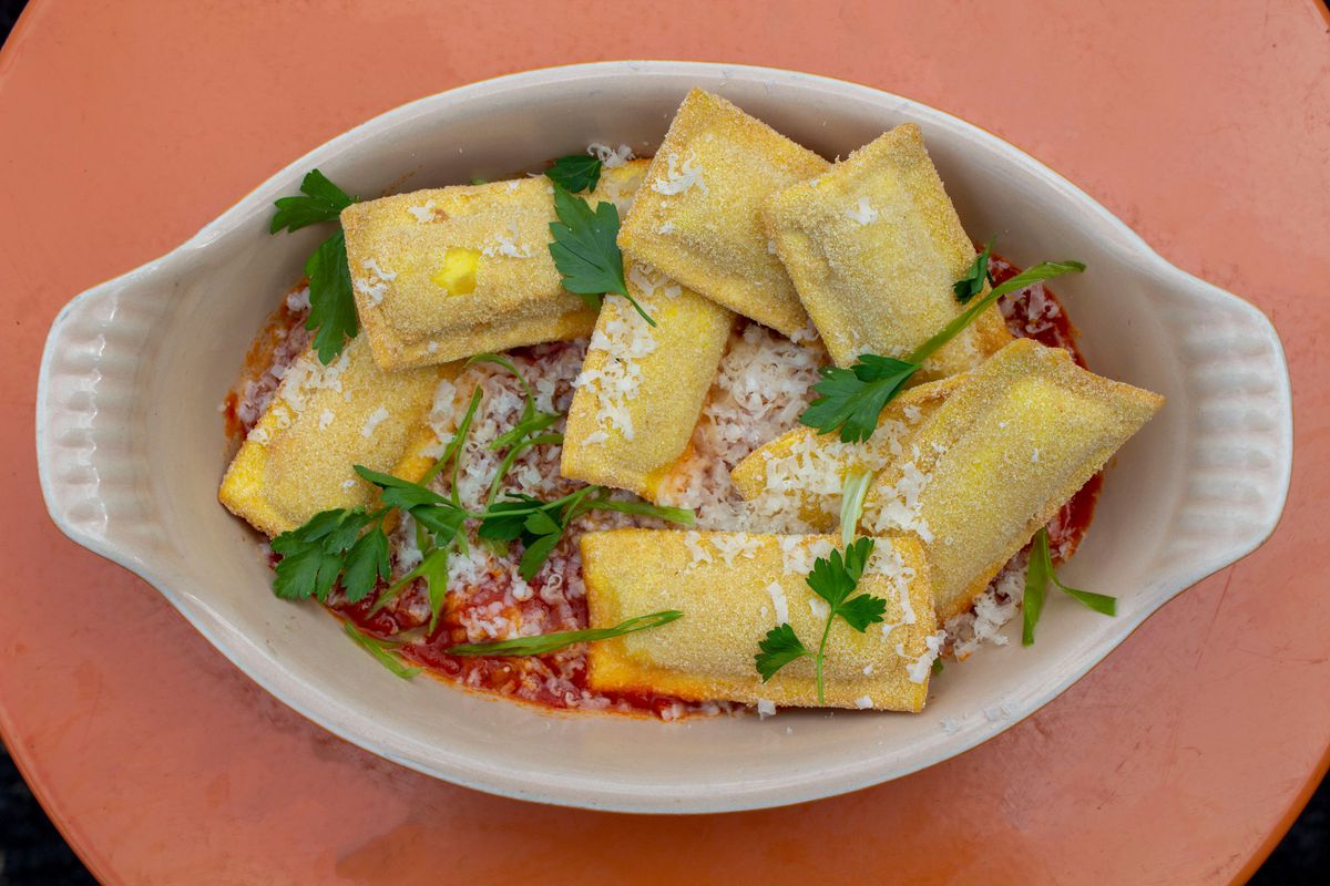 a dish of deep fried ravioli on a bed of marinara, dusted with cheese and parsley