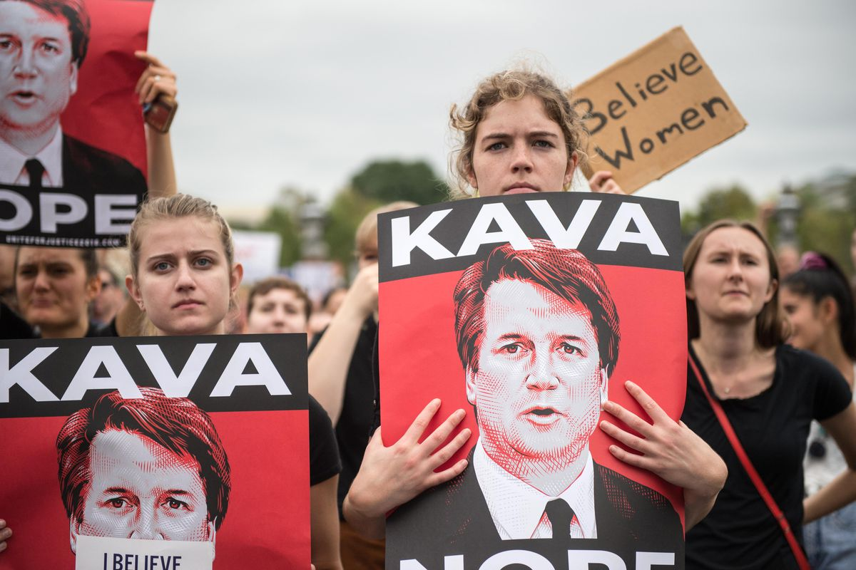 """Women carry read and black signs reading, """"Kava - Nope"""""""