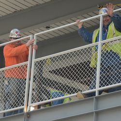 11:42 a.m. Another section of fence being welded into place. Note the worker waving at the camera -
