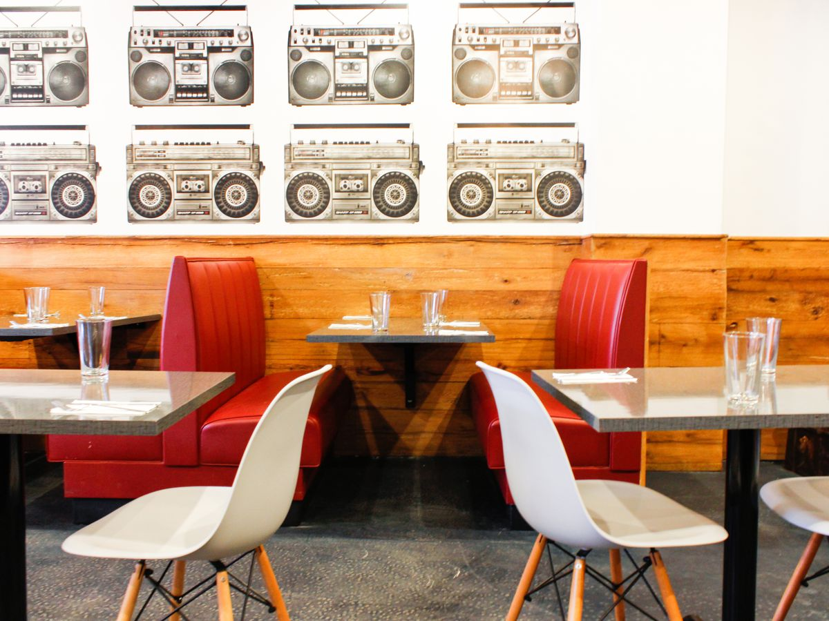 Casual restaurant interior featuring red booths and a large boombox pattern on the white wall.