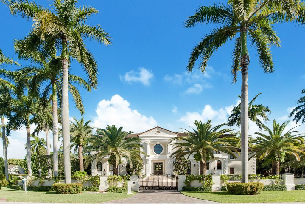 A large home in Coral Gables with giant palms on either side of the home