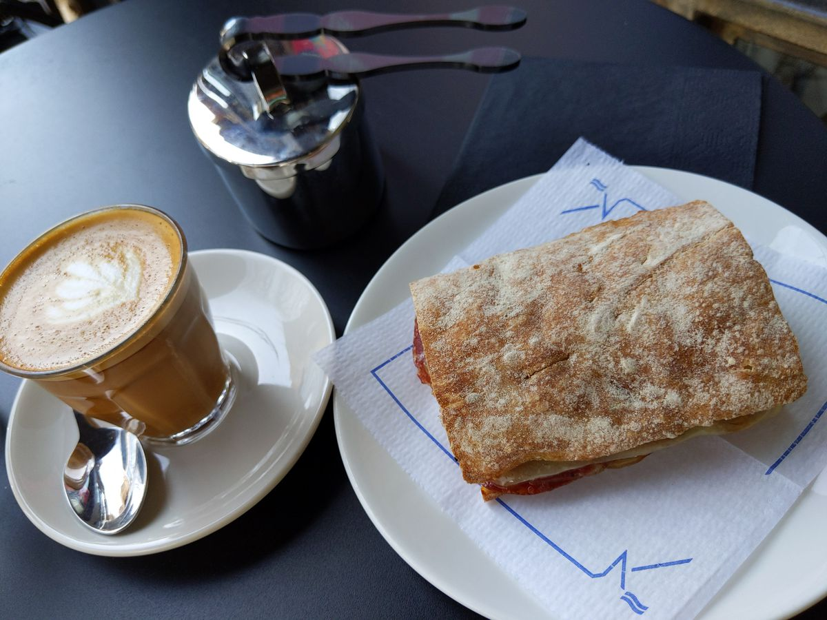 A cortado on the left and a tiny sandwich on the right, dramatically lit on a black tabletop.