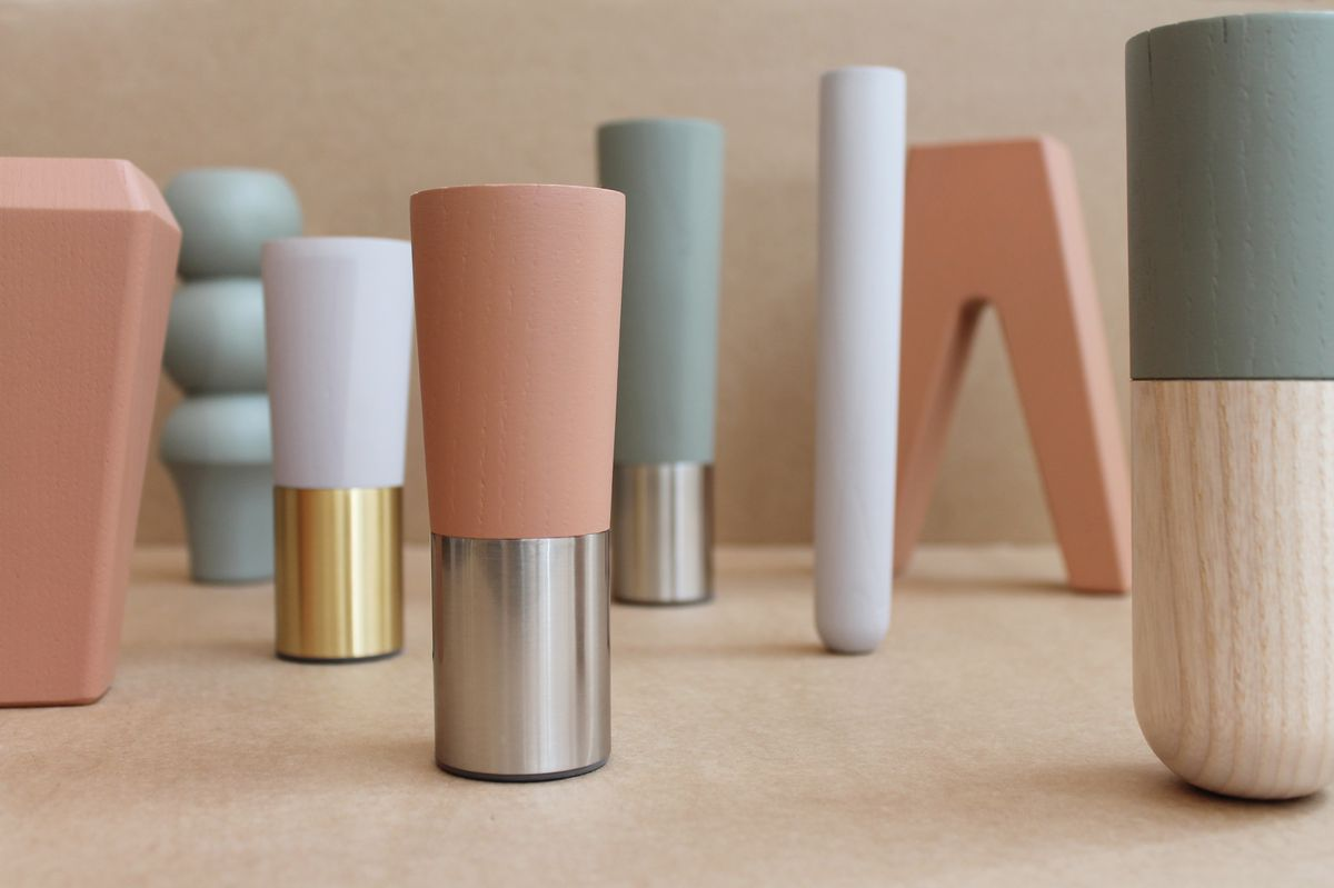 A collection of colorful cabinet legs on a table in terracotta, sage, and gray.