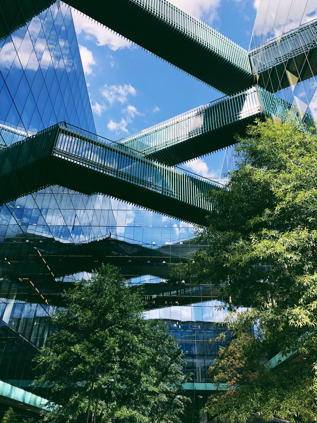A close-up of an all-glass building with multiple walkways that form a geometric pattern. The building stands high with a group of trees below.