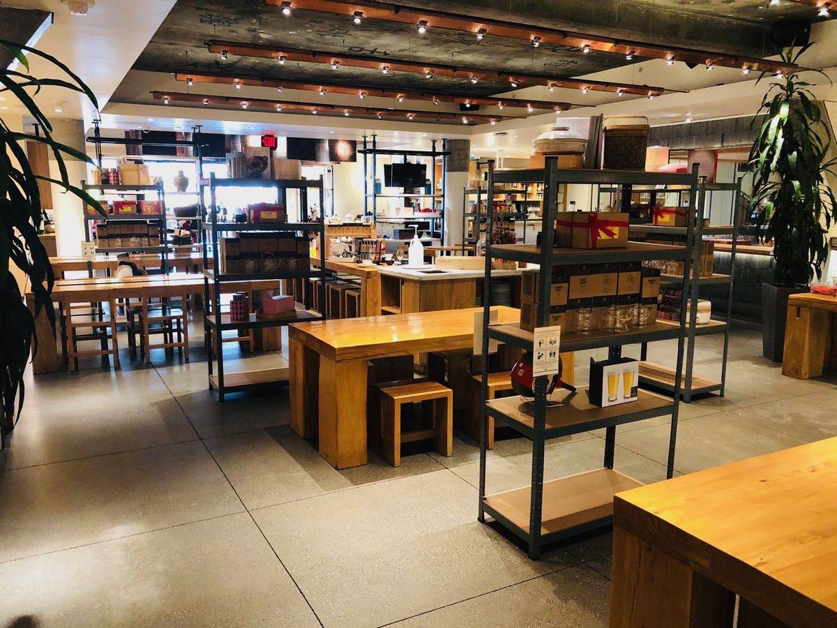 A view of the China Live dining room with shelves of retail items — cookware and so forth — in between the various tables