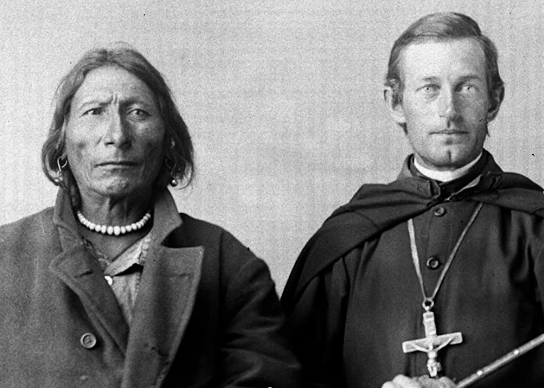A Native American man and a white man in priest's garb sit looking at the camera in a black-and-white photograph.