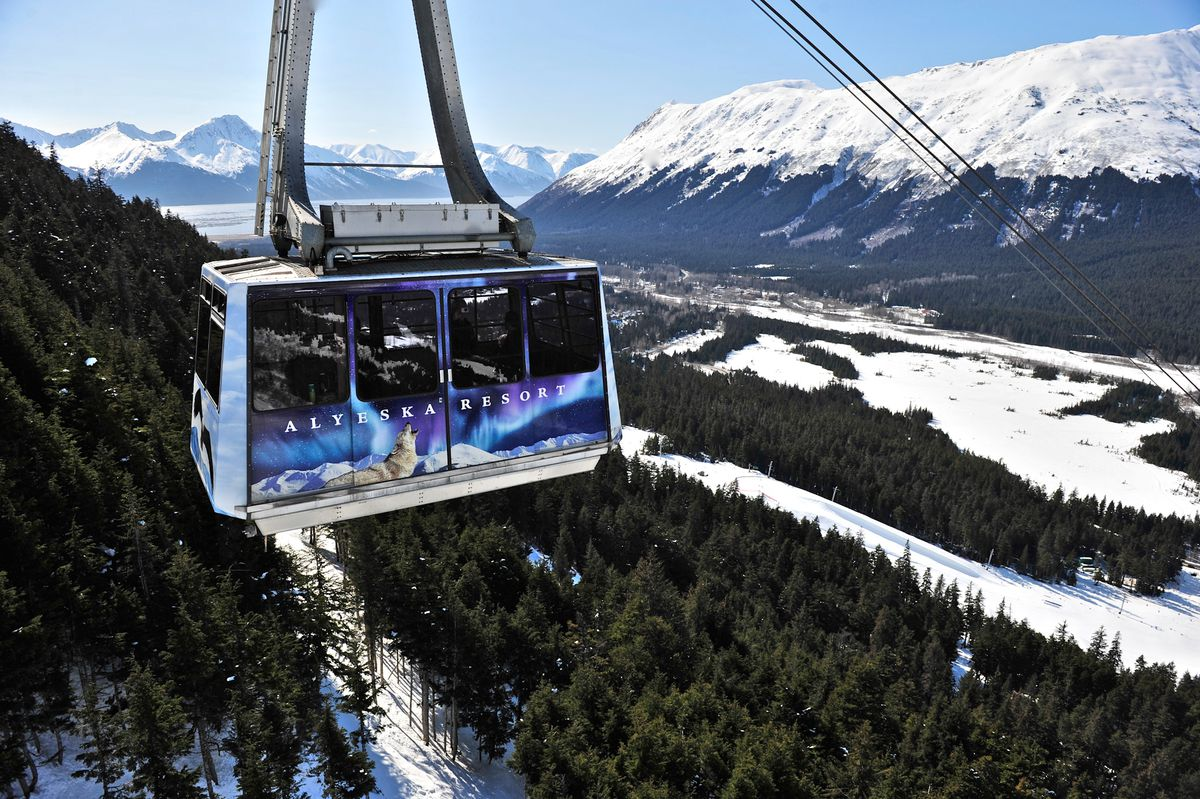 The Alyeska Resort Tram is traveling on cables over mountains covered with trees and snow.