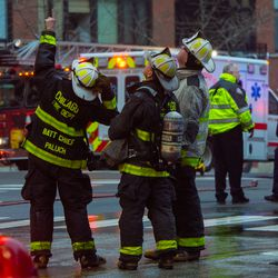 Chicago Fire Fighters point up to the top of the parking structure where official say where the fire originated, Saturday, Dec. 21, 2018, in Chicago. | Tyler LaRivere/Sun-Times