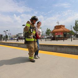 """A firefighter helps a """"victim"""" to safety during """"Hell on Wheels,"""" a full-scale, two-day, emergency protection and response drill at the Salt Lake Central Station on Tuesday, Aug. 8, 2017. The drill included emergency personnel from the Utah Transit Authority, the FBI, Salt Lake County Emergency Management, the West Valley and Salt Lake City fire departments, University of Utah Emergency Management, the University of Utah Police Department, Amtrak, Union Pacific, Murray Victim Advocates and Utah State Medical Examiner's Office. The drill simulated multiple terrorists entering the Salt Lake Valley and dividing up."""