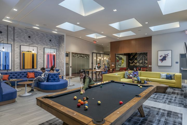 A billiard room with couches and young people.