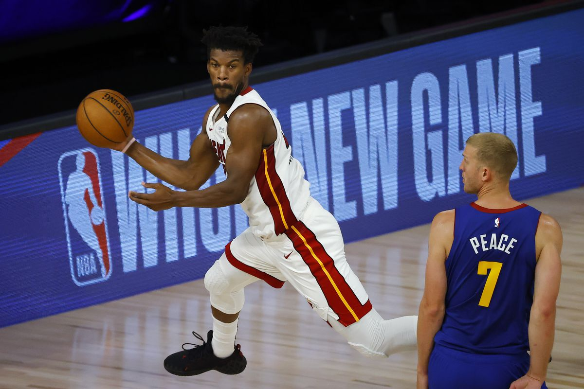 Jimmy Butler of the Miami Heat tries to save the ball from going out against Mason Plumlee of the Denver Nuggets at HP Field House at ESPN Wide World Of Sports Complex on August 01, 2020 in Lake Buena Vista, Florida.