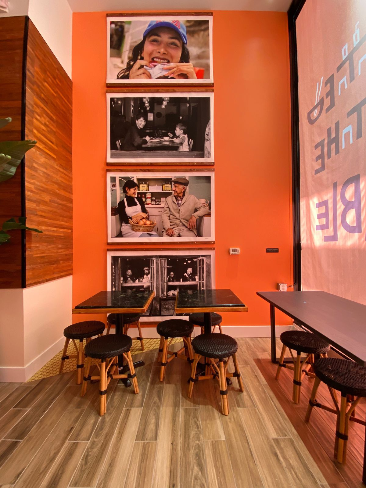 Photos on the wall by stools and tables at Immigrant Food