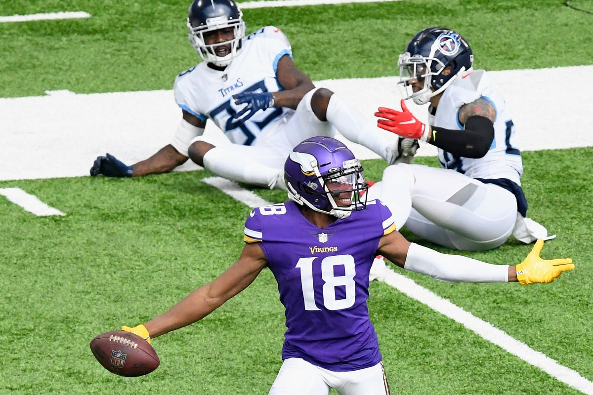 Justin Jefferson #18 of the Minnesota Vikings avoids a tackle by Kenny Vaccaro #24 and Johnathan Joseph #33 of the Tennessee Titans during the third quarter of the game at U.S. Bank Stadium on September 27, 2020 in Minneapolis, Minnesota. Jefferson scored a touchdown on the play.