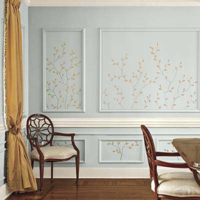 Blue walls with decorative paint pattern in the shape of twigs.
