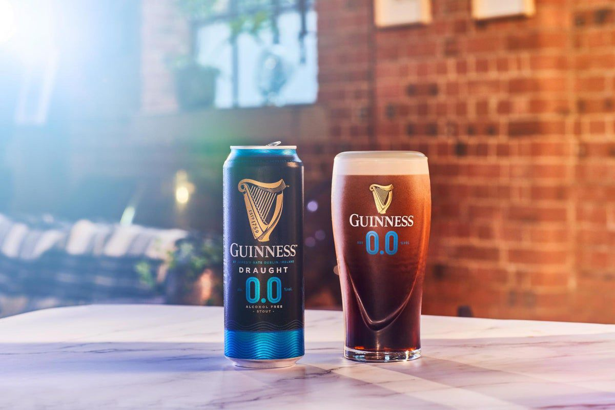A can of Guinness 0.0 stout, next to a full pint of the same beer, in a Guinness-branded class with its harp logo