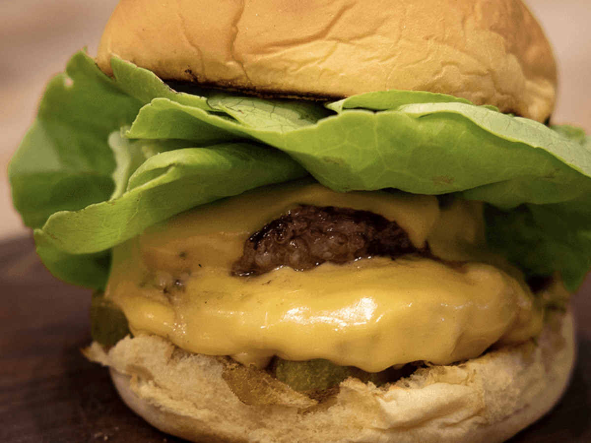 A close-up photo of a cheeseburger topped with several pieces of lettuce