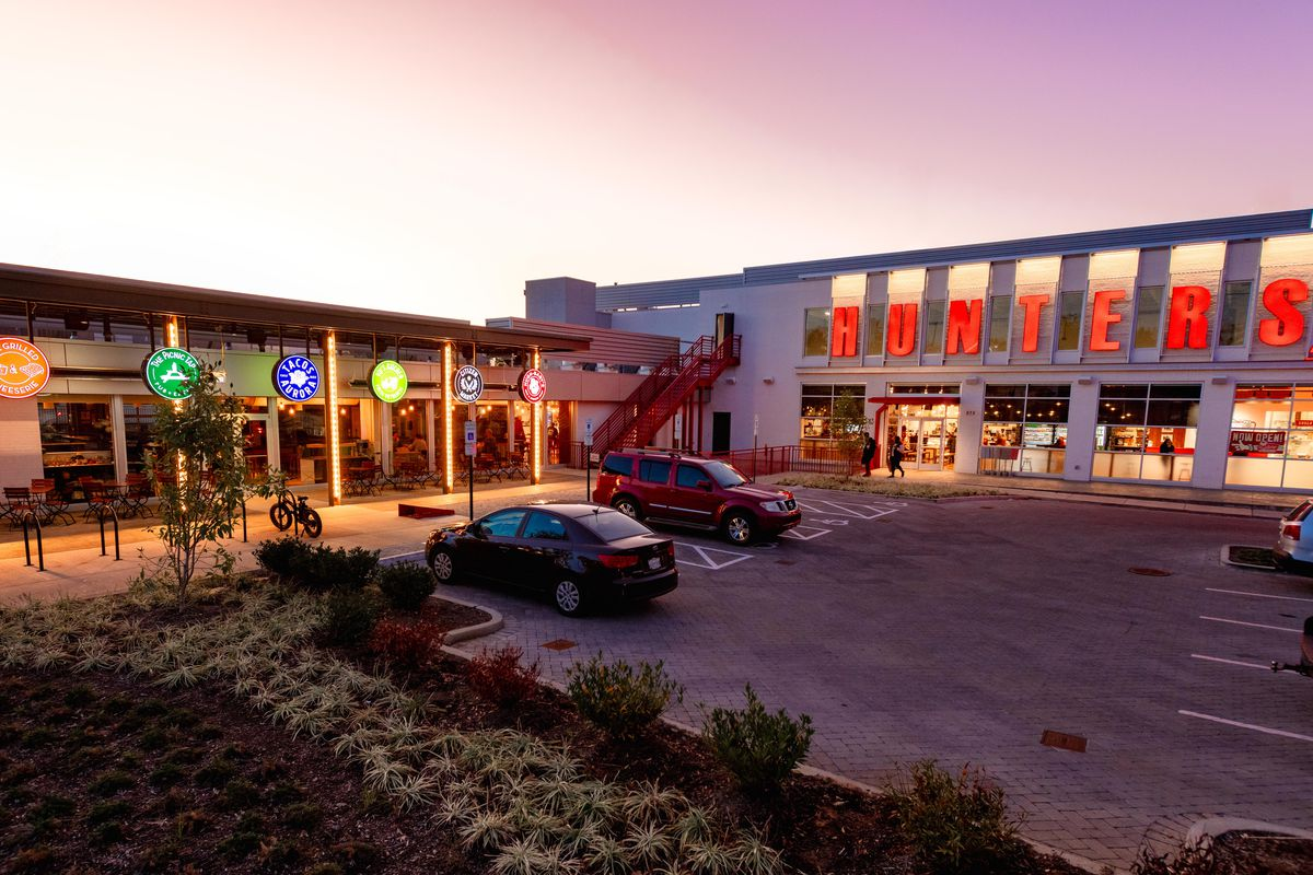 exterior shot of building at night, cars in parking lot