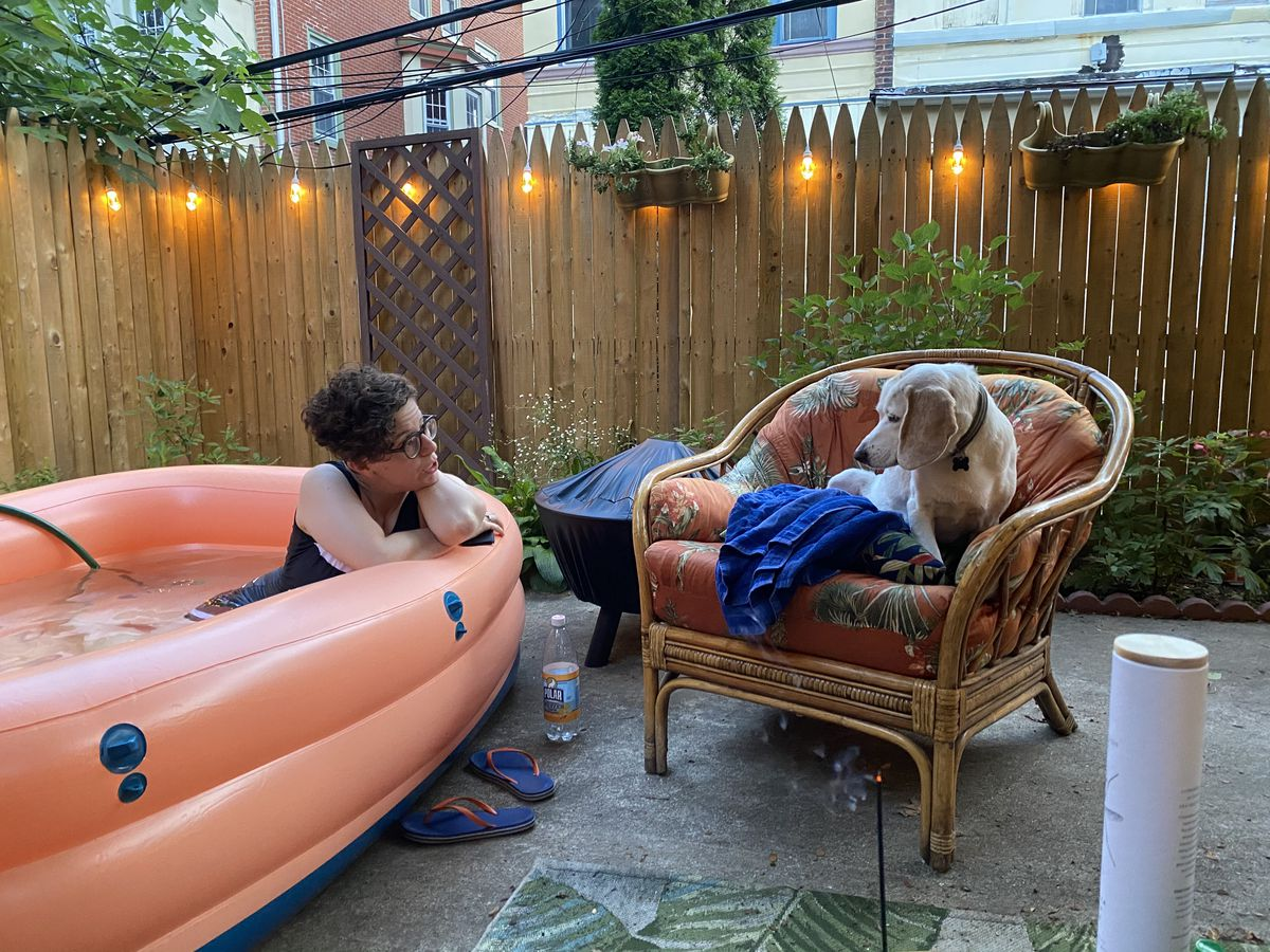 a woman in a pink inflatable pool talks to a dog.