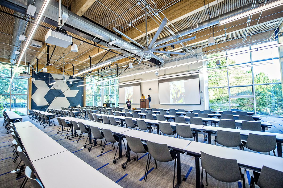 A lecture hall show with many seats and huge windows on all side.