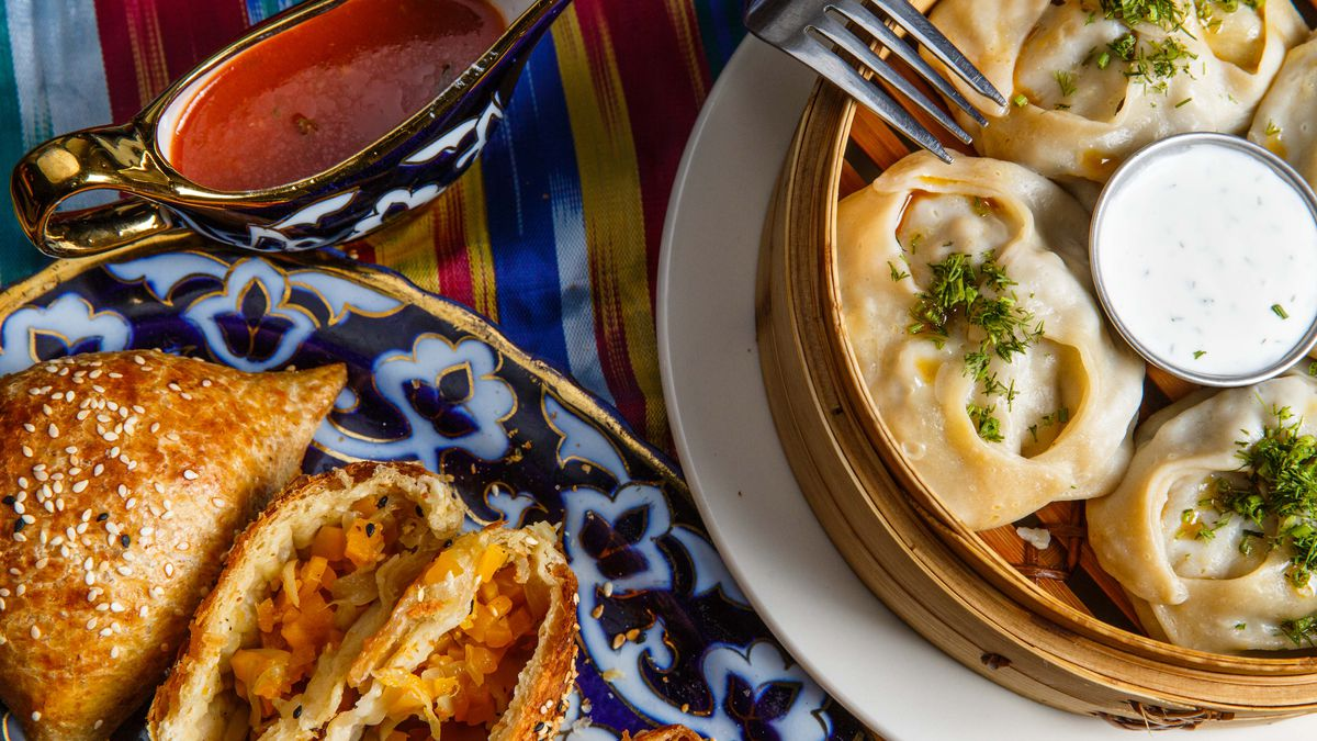 Pumpkin samsa turnovers sit in a steamer while lamb manti dumplings sit over a decorative blue and white plate