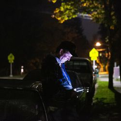 Matthew Branstetter checks his phone outside one of the vehicles he and his family live in at Lake Washington United Methodist Church in Kirkland, Wash., on Saturday, Oct. 12, 2019. Branstetter and his family have been using the Safe Parking program for the past several months, first becoming homeless in December 2018. Branstetter, who has been doing Instacart deliveries during the day, is waiting to hear back about millwrightposition.
