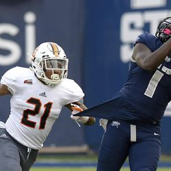 Utah State wide receiver Ron'quavion Tarver (1) catches a pass as Idaho State defensive back Brandon Monroe (21) defends during an NCAA football game Thursday, Sept. 7, 2017, in Logan, Utah. (Eli Lucero/Herald Journal via AP)