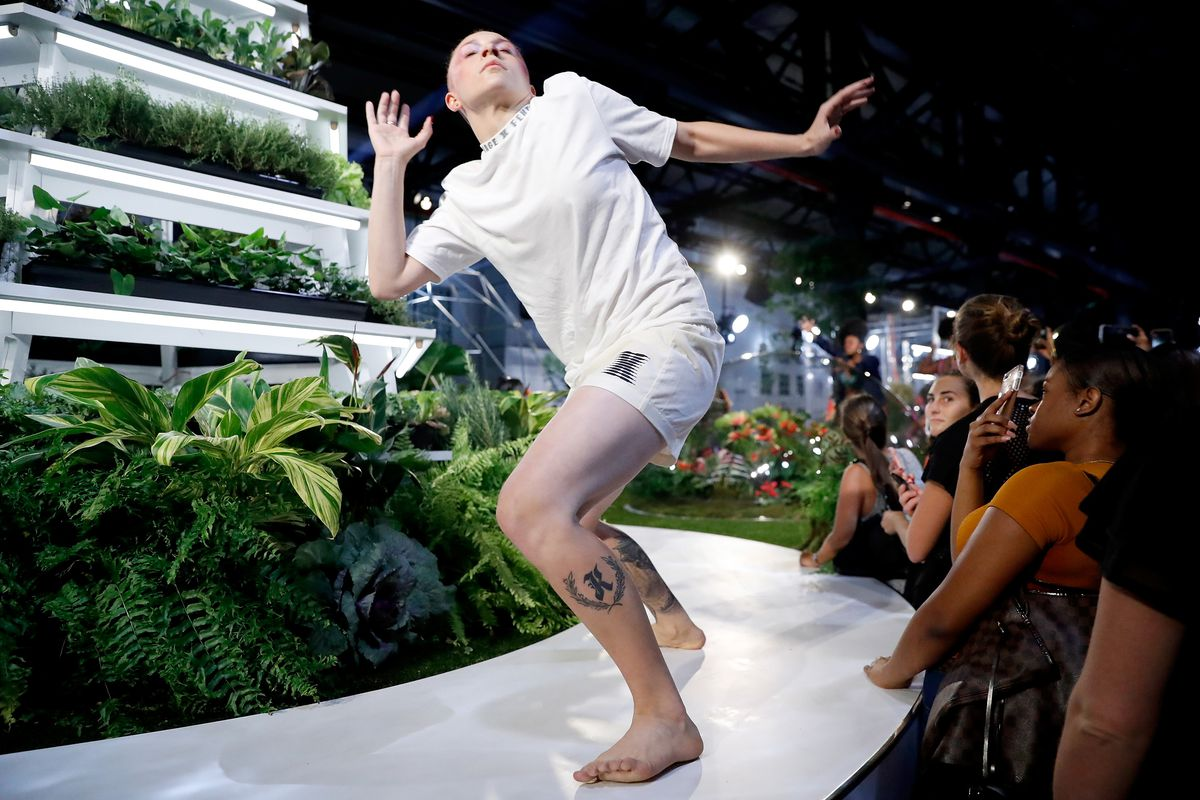 A dancer wearing a white T-shirt and boxers performs.