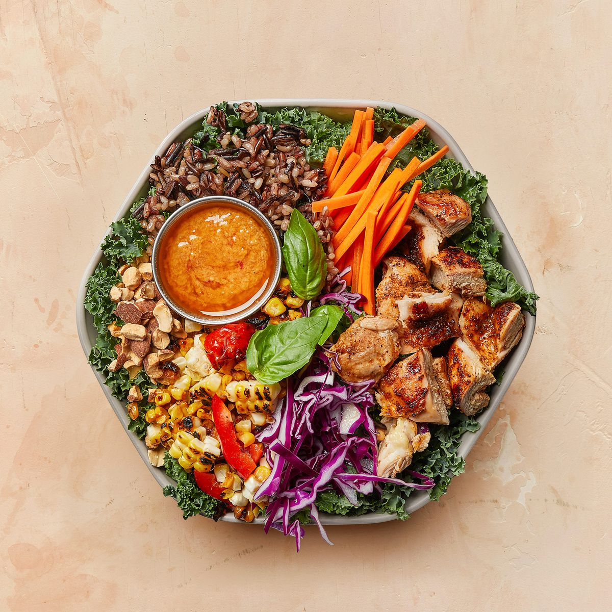 Hexagon tin bowl containing a bed of kale green with a colorful variety of nuts, grains, purple cabbage, grilled chicken, julienned carrots, and corn with a sprig of basil leaves
