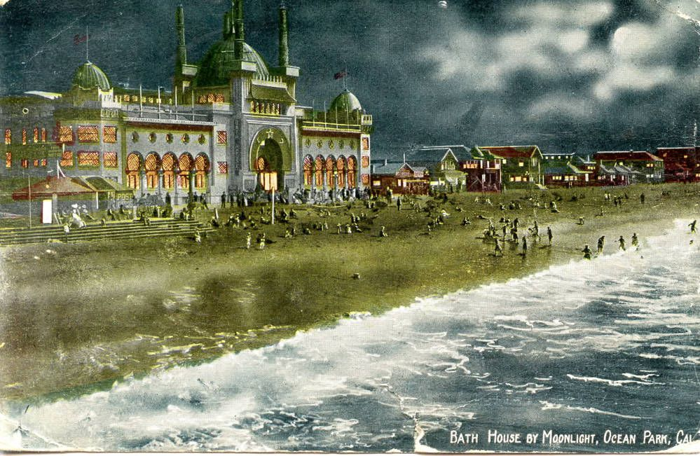 A colorful vintage postcard of an ornate bath house at night. The waves lap at the sandy shore, illuminated by moonlight.